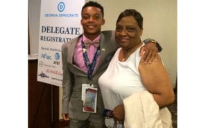 Kendall Austin waits in the hotel lobby with his grandmother, Sandra Austin, chairwoman of the DeKalb County Democratic Party, before boarding the delegate bus to the Wells-Fargo Center in Philadelphia.