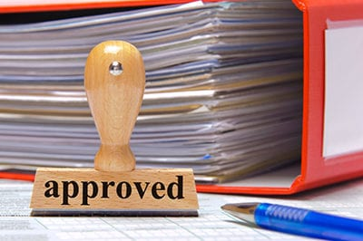 rubber stamp in office marked with approved
