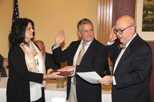 Vince Evans is sworn in as his wife, Cyndi, holds the Bible before Chief Superior Court Judge David Irwin.