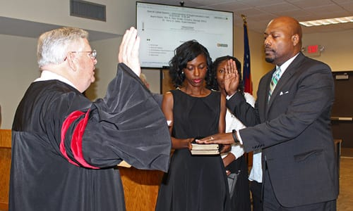 Rockdale County Public Schools Superintendent Dr. Terry Oatts–accompanied by his wife Yolanda, daughter Teryn, and son Landon–is sworn in by Rockdale County Superior Court Judge Robert Mumford.