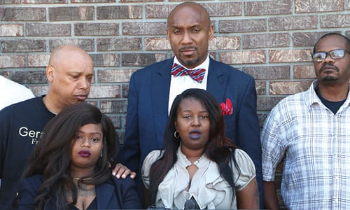 Attorney Mawuli Davis (back), community organizers and Tilson's family held a news conference on May 4 to urge witnesses to come forward. Photo by Glenn L. Morgan