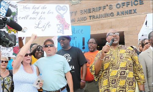Derrick Boazman ( holding the microphone) is flanked by Jamie Henry's parents at left. Photos by Glenn L. Morgan