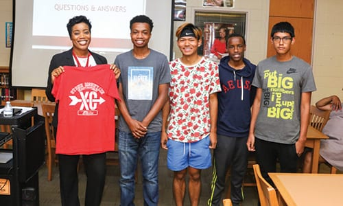 L-R: Stone Mountain principal Dr. Wislene John receives a t-shirt and is made an honorary member of the cross country team by members Marcus Wilson, Kun Aung, Mohamed Nuur and Oliver Ochoa.
