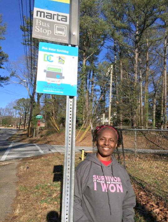 Priscilla Davenport, breast cancer survivor, stands in front of her adopted MARTA bus stop she has sponsored for the past two years.