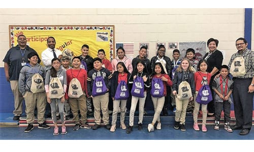 """Dresden Elementary School principal, Dr. Jesse Berger, school staff, DWM staff, and fourth and fifth-grade students pose with """"No FOG, No Clog"""" backpacks. Photo provided"""