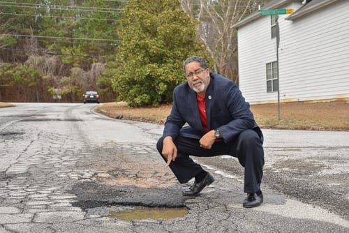 Stonecrest Mayor Jason Lary points out pothole in the Chestnut Lake subdivision. Photo provided