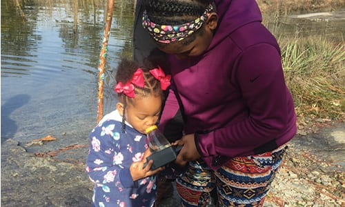 """Sisters Aniyah, 12, and Amelia Brown, 3, use a handheld microscope to identify samples collected at Davidson-Arabia Mountain Nature Preserve for """"Hike and S'mores with the Rangers"""" on Saturday, Dec. 29."""