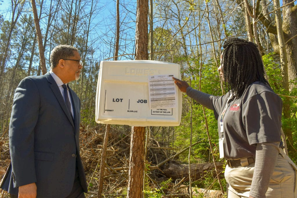 Mayor and Darkota in front of cell tower violation notice